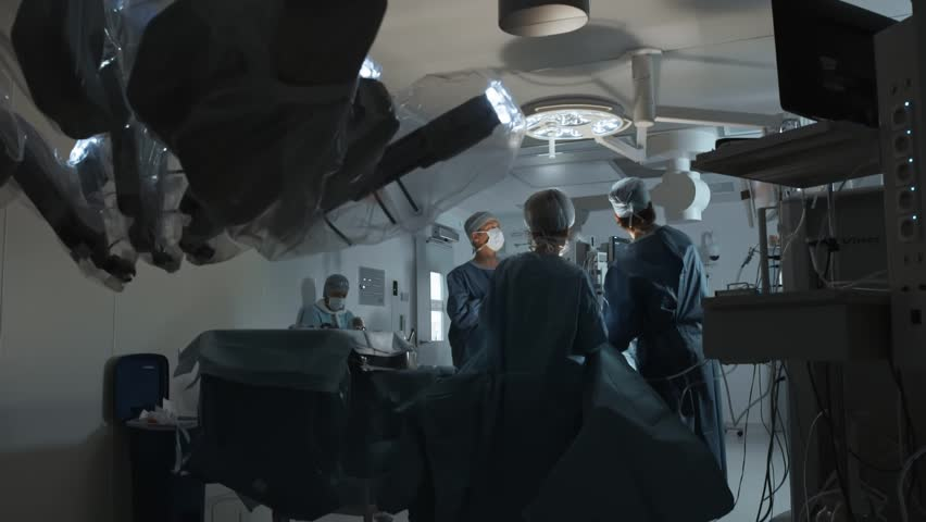Operating room, team of surgeons prepares patient to cancer removal surgery via Minimally Invasive Robotic Surgery  Hi-tech medical robot | Shutterstock HD Video #1010832131