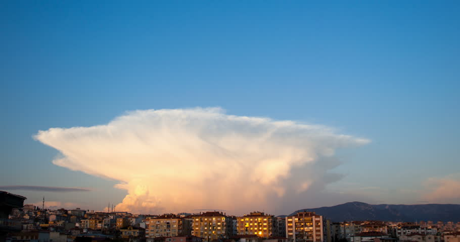 Cumulonimbus Capillatus clouds with some cumulus clouds while getting dark and sun going down.