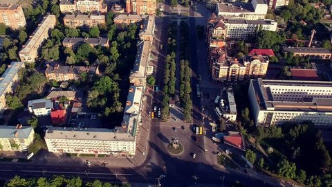 Main Poltava city square with cars and trees in sunrise light.