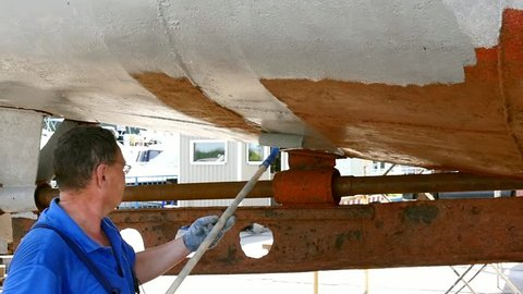 Worker paints metal of old rusty ship propeller at shipyard in port. Process of repair and reconstruction of sea vessel. Technology of manual painting boats. Industry of water transport.