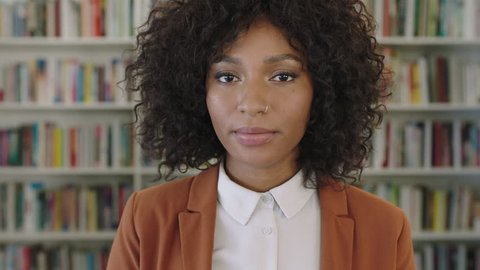 close up portrait of stylish african american business woman intern looking serious pensive at camera in library bookshelf background real people series