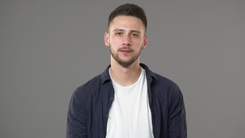 Portrait of good-looking guy in casual clothing posing with doubting look while thinking or weighing pros and cons, isolated over gray background. Concept of emotions
