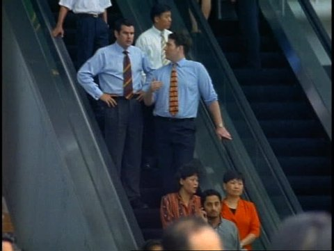 SINGAPORE, 1999, Singapore financial district at noontime, man on escalator talks on cell phone