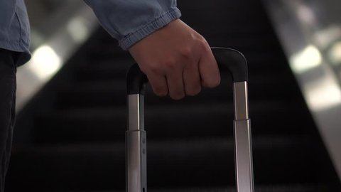 4k, Young women hand on pulling suitcase on escalator in modern airport terminal. Traveling,wearing smart casual style clothes walking away with her luggage waiting for transport. Rear view. Close-up
