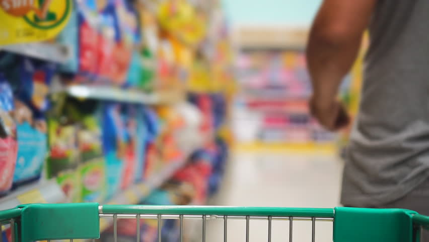 Man in the shopping center choosing goods. Choosing and inspecting the food product. Rows of shelves with goods and products.    Shutterstock HD Video #1010935541
