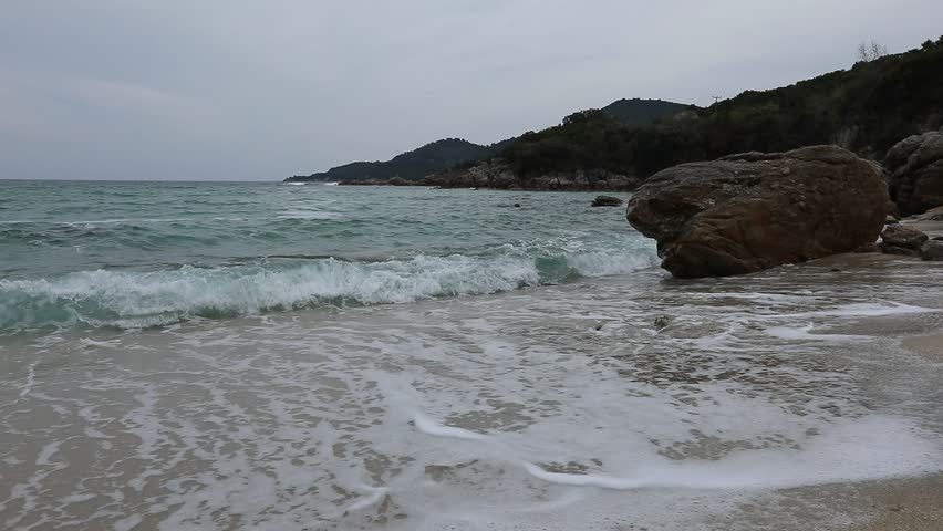 Proti ammoudia beach near Olympiada town summer resort, Kavala region, Greece. Rocks and waves in different plans. Original video without processing 60 frames per second