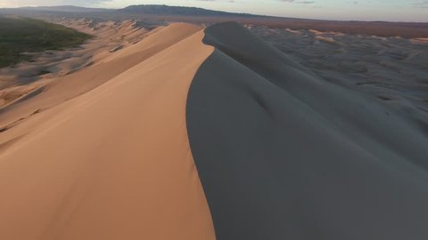 Aerial drone shot flying over the crest of a giant sand dune in gobi desert Mongolia. Sunrise time, oasis on the left and mountains in background. Low altitude flight.
