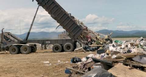 Large dump truck emptying a dumpster of construction and household trash at a landfill, or junkyard