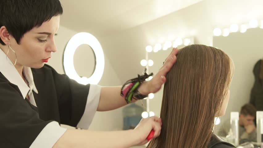Hairdresser combing long hair before female haircut in hairdressing salon. Close up woman hairstyle in beauty salon. Hairdresser preparing to haircutting wet hair   Shutterstock HD Video #1011014231
