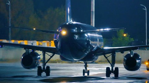 Airplane riding on the runway before take off at night. Rear view