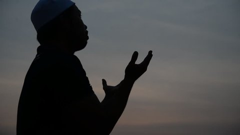 Young asian muslim man praying on sunset,Ramadan festival concept,Thailand people,Blessings from the Allah,