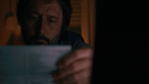 Worried freelance entrepreneur reading a letter in dark home office interior, low key footage with selective focus