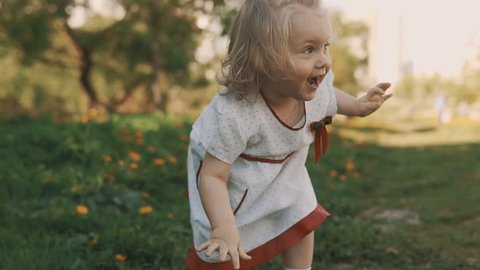 Funny Little Girl Running Away from Her Mom. Mother and Daughter in Dress Playing Together Enjoying Warm Summer Weather in Park in Slow Motion