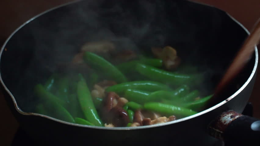 Slow motion clip: Fried vegetables, sugar snap pea, mushrooms and shrimps in hot pan. Healthy food concept.