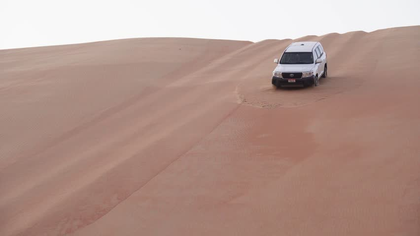 Abu Dhabi, UAE - April 05, 2018: SUV descends from a high dune in the Rub al Khali desert stock footage video #1011076271
