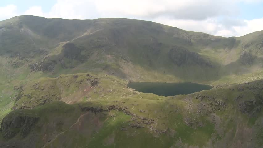 Aerial footage of The Lake District mountains and Lake Windermere, England, UK. We see a deep, secluded, isolated pool of water. The camera turns to reveal Lake Windermere. Shot in HD from Helicopter.
