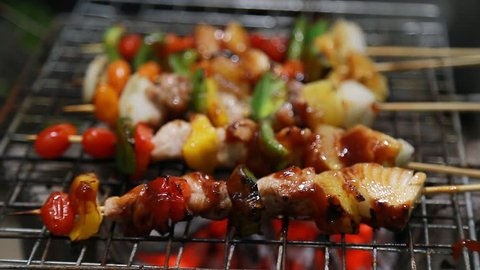 Close up assorted delicious grilled meat with vegetables over the coals on a barbecue