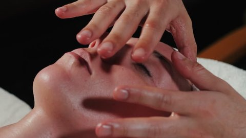 Closeup of young woman receiving professional head and face massage. Leisure. Girl enjoying anti-aging facial massage treatment in beauty spa salon. Slow motion.