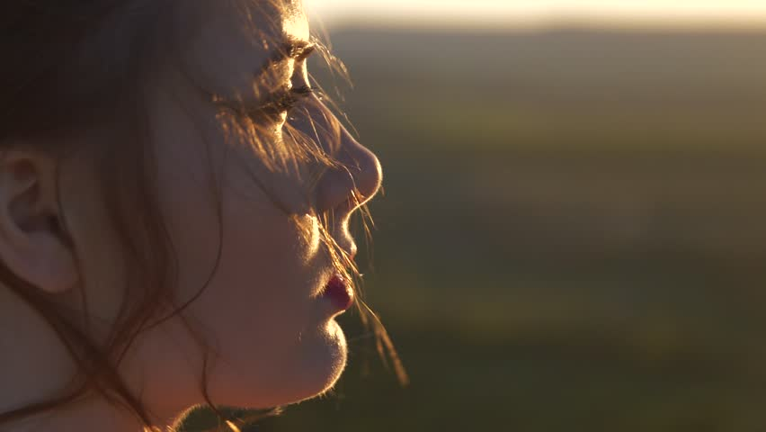 The face of a young beautiful woman who looks at the setting sun The wind shakes her hair | Shutterstock HD Video #1011129071