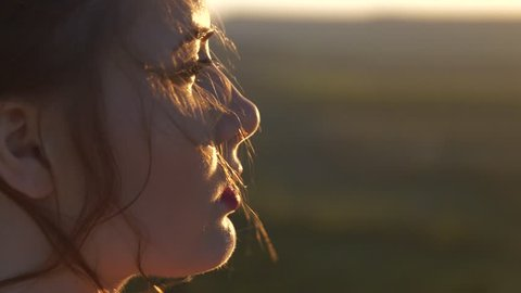 The face of a young beautiful woman who looks at the setting sun The wind shakes her hair