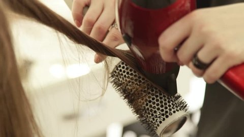 Haircutter using dryer for drying female hair and hairbrush for styling after hairdressing in beauty studio. Close up hairstylist making hairstyling long hair in hairdressing salon