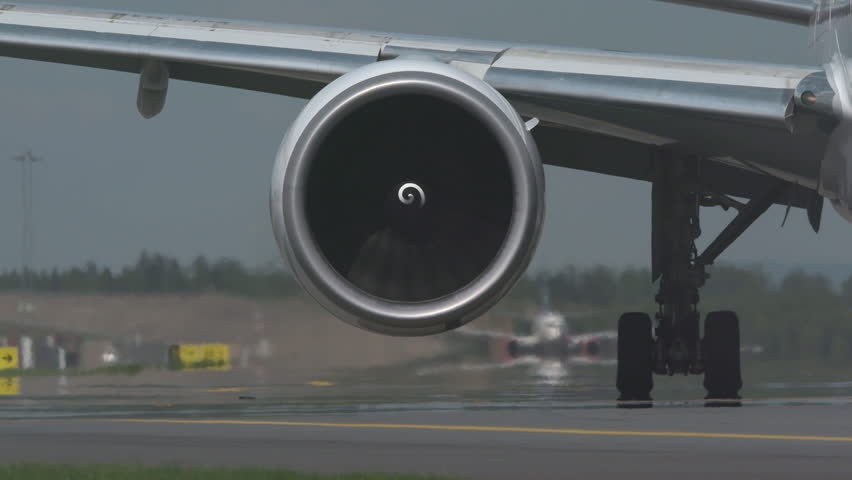 Huge airplane jet engine close up view moving forward heat haze distant airplane lining up behind