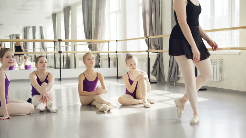 Ballet teacher experienced ballerina is dancing on tiptoes demonstrating movements to her little students sitting on floor, watching tutor then clapping hands.