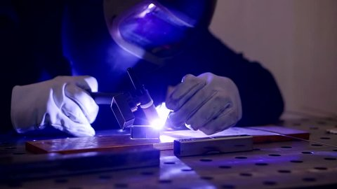 Close up shot of a mechanic who is engaged in the argon welding of an aluminum product