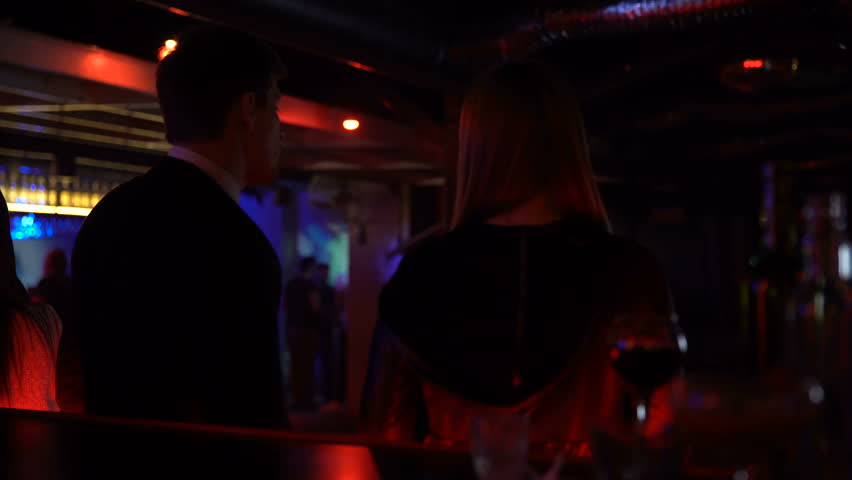 Couple dancing and talking at bar counter, acquaintance in nightclub, back view   Shutterstock HD Video #1011216041