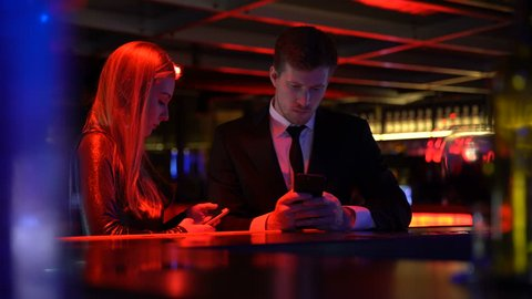Young bored couple obsessed with smartphones, internet addiction ruins relations