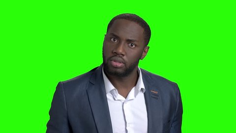 Afro-american businessman showing silence gesture. Portrait of young serious businessman placing finger on lips saying shhh, be quiet on chroma key background. Human body language.