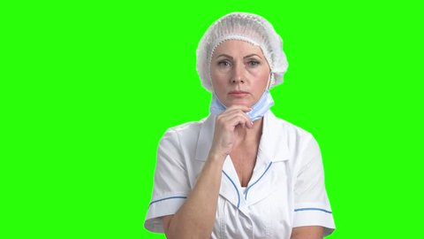 Shocked female doctor on green screen. Doctor woman in cap and mask looking horrified on chroma key background. Human expressions of grief.