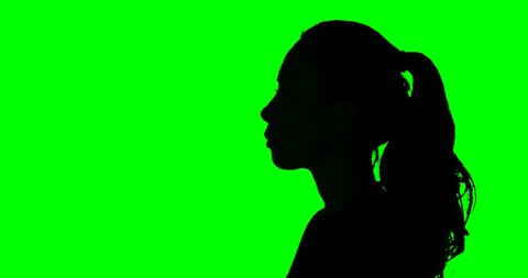 Silhouette of unidentified woman talking with a megaphone in the studio. Shot in 4k resolution with green screen background
