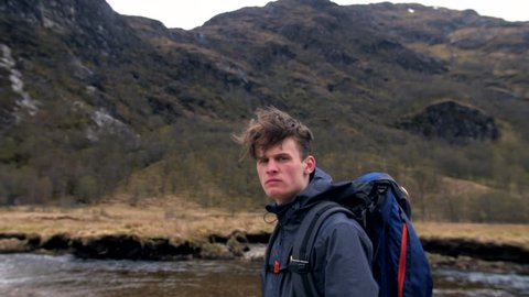 4K Young traveller hiker portrait looking at camera in front of Steall waterfall Scottish Highlands UK. A man backpacking nature path  and trekking through mountains in Scotland in slow motion