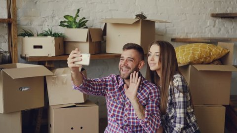 Happy young couple is making video call with smartphone after relocation. They are greeting friends, showing new house keys and boxes, chatting and smiling.