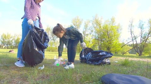 teen girl and woman volunteers collect garbage in the park in plastic bags