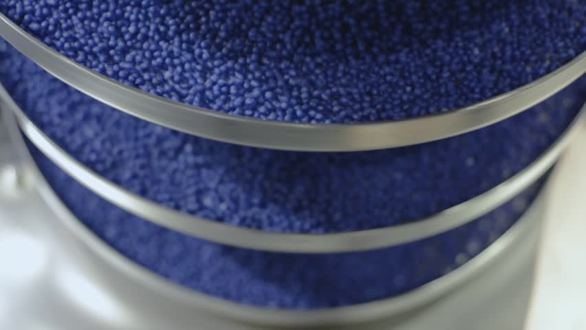 Vertical vibrating conveyor. The blue round granules move up the vibrating screw conveyor.