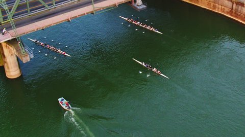 Drone Aerial view of sweep Rowing boats passing under the bridge while traffic and cyclists and runners pass over it