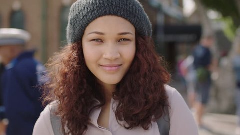 portrait of pretty mixed race girl laughing cheerful in city street wearing beanie hat
