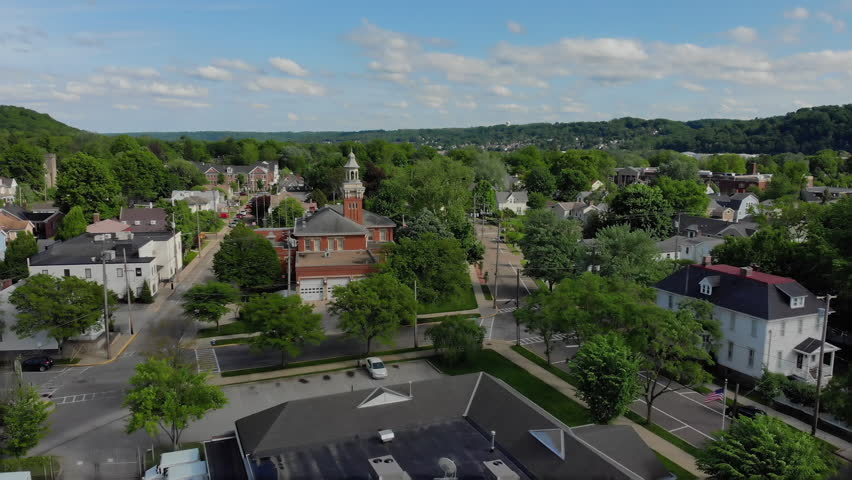 A slow moving forward wide aerial establishing shot of the steeple of a city hall in the small New England town. Pittsburgh suburbs.