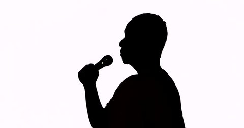 Silhouette of a male singer singing a song with a microphone and classical gesture in the studio, isolated on white background. Shot in 4k resolution