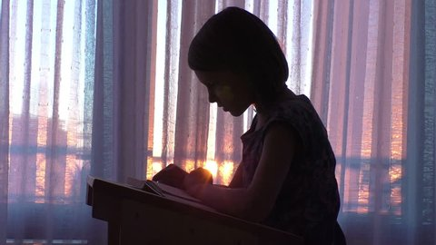Young cute girl silhouette reading book in classroom at the sunset