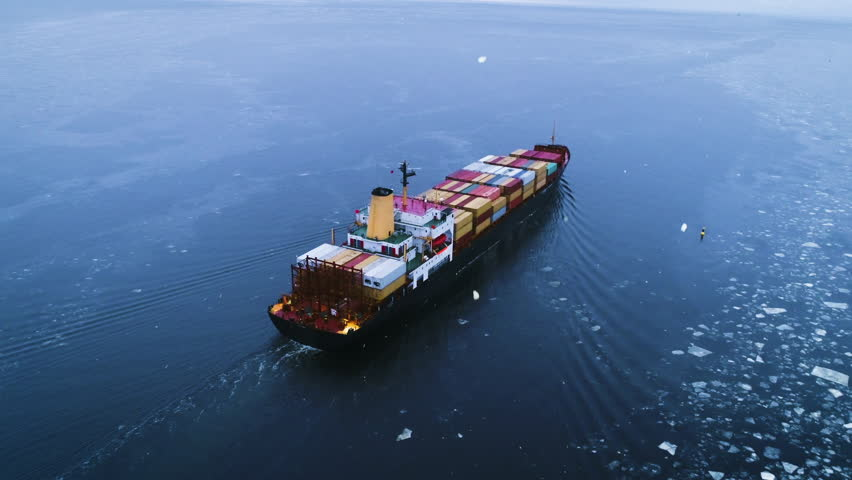 Aerial Shot of the Cargo Ship Moving Through the Sea. In the Background Winter Landscape. Shot on 4K UHD Camera.