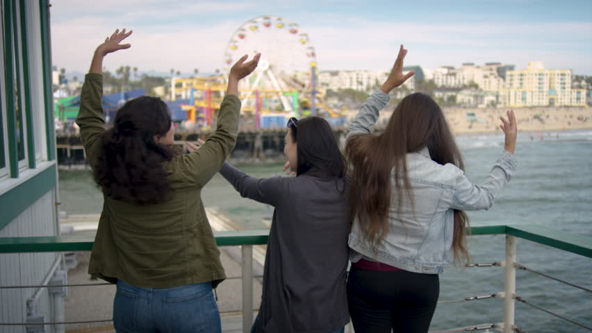 Group Of Girlfriends Put Their Arms In The Air And Do A Silly Dance, Then Laugh (Santa Monica Pier In Background) - Shot On Red Scarlet-W Dragon In 4K, Slow Motion | Shutterstock HD Video #1011346841
