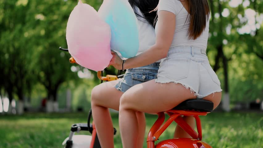 Two young and sexy brunette friends with loose hair in short denim shorts riding an electric motorcycle in the Park. Close-up view from the back side. Beautiful buttocks on a scooter on a Sunny day