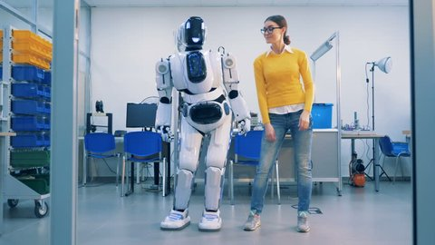 Young woman is dancing with a robot who spanks her playfully after whereafter she leaves