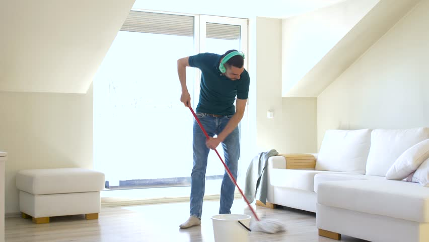 People, housework and housekeeping concept - happy man in headphones with mop cleaning floor and dancing at home | Shutterstock HD Video #1011373571