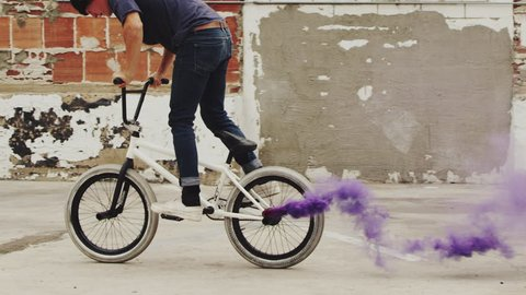 Extreme BMX biker doing tail whip with purple colored smoke grenade in slow motion