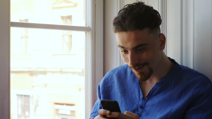 attractive surprised bearded caucasian man looking shocked at smartphone screen checking notification good news