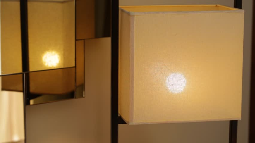 Closeup view of lamp on table in interior. Turning light on and off using dimmer control.